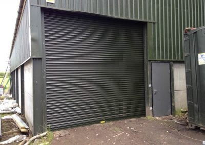 A steel hinged personnel door and adjacent roller shutter