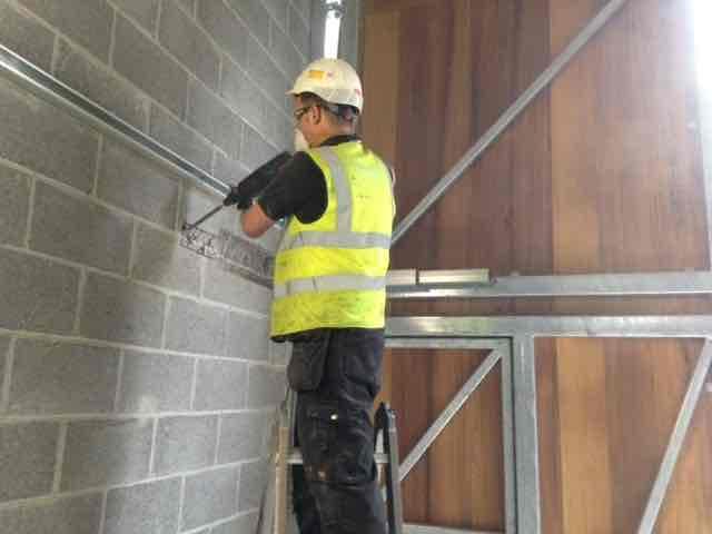 Industrial Door Servicing - Engineer Repairing Door